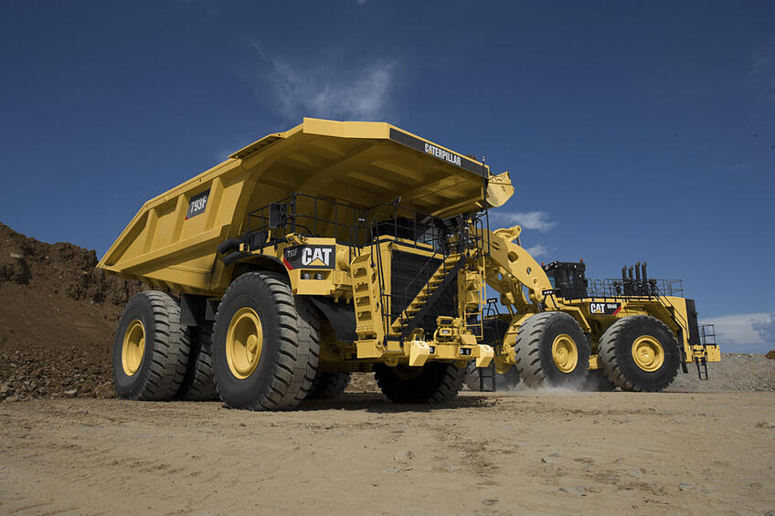 Cat-793F-mining-truck-being-loaded-by-Cat-wheel-loader-1100x733