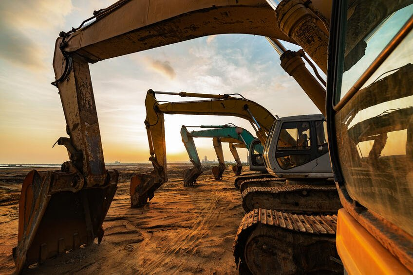 multiple-excavators-parked-heavy-construction-equipment